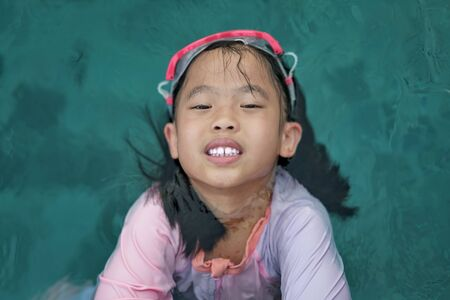 Girl with goggles in pool water smile at camera in pool play portrait concept