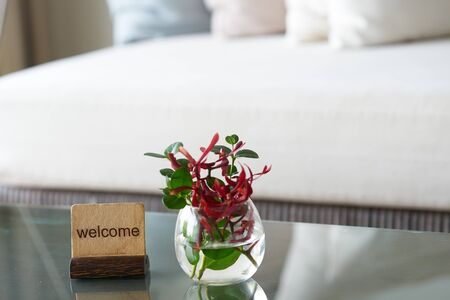 Welcome label stand with flower water vase on table with sofa background for welcome reception concept
