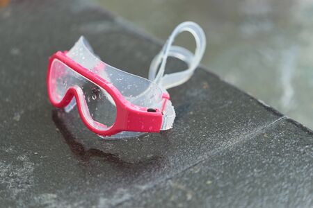 Water swimming goggles on pool side