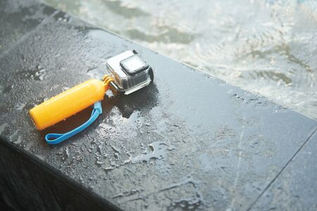 Action camera in water proof case and floating hand grip on pool side