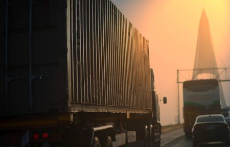 side view of container truck with blur bridge background