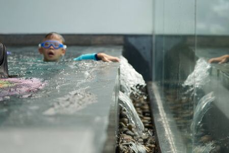 Kids play water in pool with water fall off in vacation concept