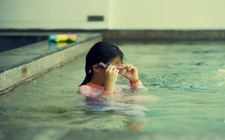 Girl plays water alone with goggles in summer time vacation