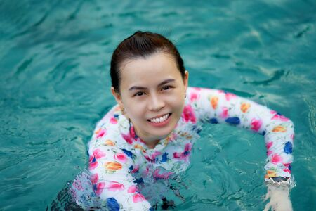 woman with goggles in pool water smile at camera in pool play portrait concept