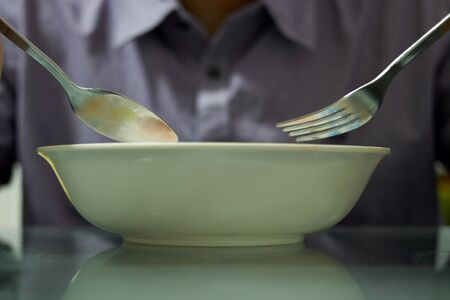 Hands hold spoon and fork with bowl to eat cerial breakfast