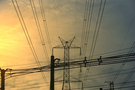Electricity wires at tower poles and mess of wires on sky background Imagens
