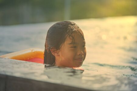 Girl play in swimmong pool in summer vacation time with happiness with flare