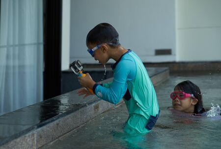 Kid use action camera while play water in summer time Imagens