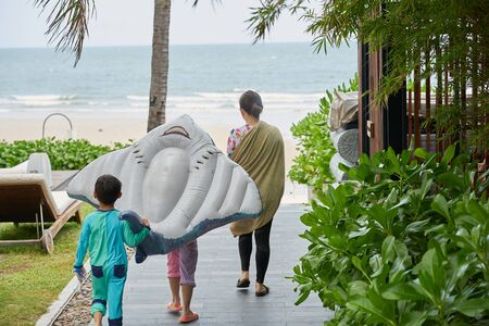 Travel family walk to the beach with toy floater in vacation concept