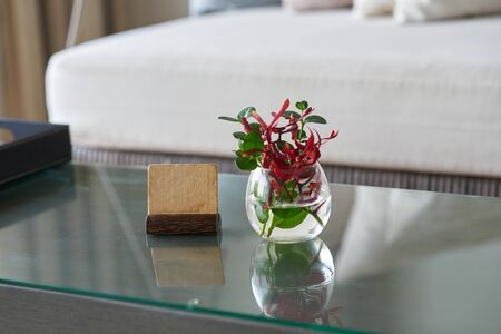 Mock up label stand with flower water vase on table  in room for welcome reception concept