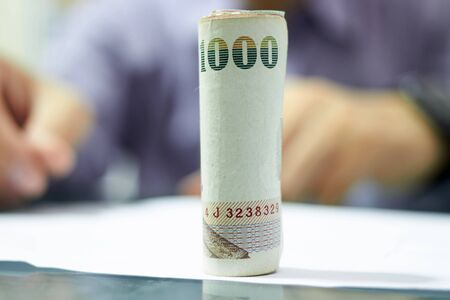 Roll of Thai baht banknotes on blur working office background Imagens