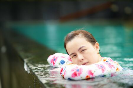 asian woman rest beside pool side look at camera in portrait vacation concept