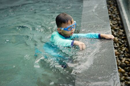 Boy plays water alone beside pool in summer concept