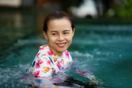 woman with goggles in pool water with smile in pool play portrait concept