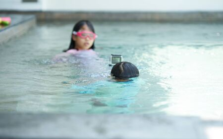 Girl play water in pool in summer vacation time with goggles and action camera