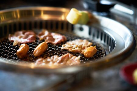 Grilling sliced pork ,sausages and Marshmallows on asian grill style