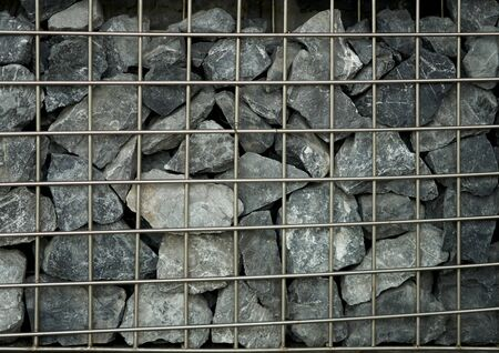 Abstract stones in metal squre cage wall for decoration Imagens