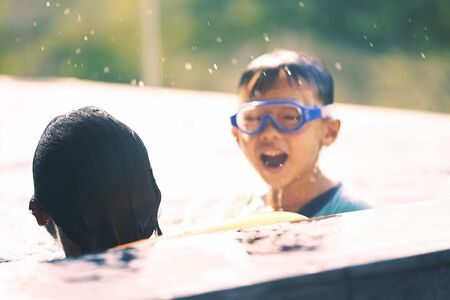 Kids play in swimmong pool in summer vacation time with happiness
