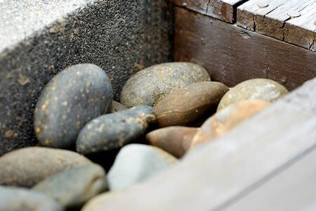 Round and oval shape Stones with concrete wall corner