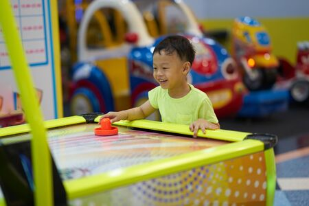 Boy plays game in arcade in mall playground concept 写真素材