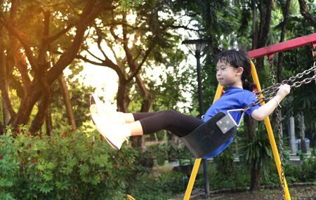 Motion blur of girl is playing swing toy in public playground in park on blur playground background in the power of youth concept
