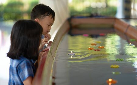 Boy and girl look at candle floater in water