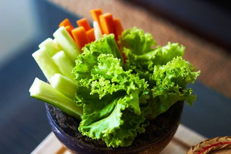 Lettuce ,cucumber and carots sliced in wooden bowl in natural diet concept