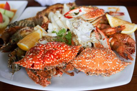 Sea food on plate include shrimps ,lemon,squid and crab shell