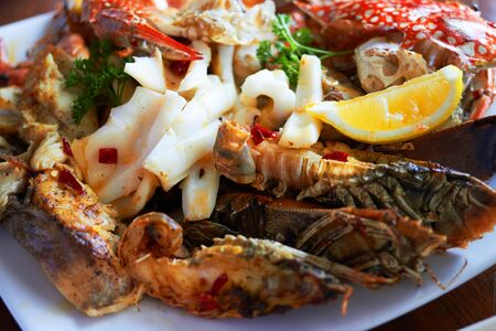 Sea food on big plate include shrimps ,lemon,squid and crab