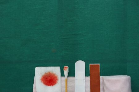 half tools includes plaster,swab,blood gauze and roll gauze on green surgical dress for clean wound with copy space 版權商用圖片