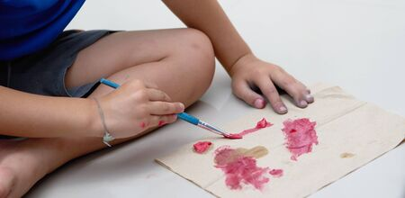 Kid hand make art activity with brush and slime coloring on paper on floor Stock fotó