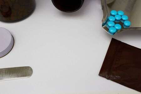 Medical background with blue coated tablets on drugstore table counter with copy space
