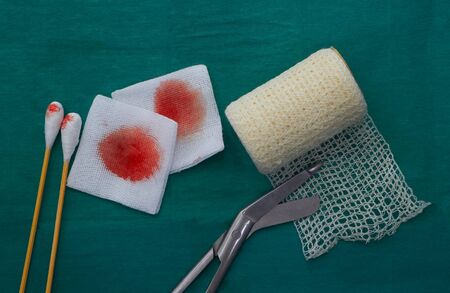 tools include scissors, swabs,net roll gauze and blood gauze on green surgical dress  for clean wound