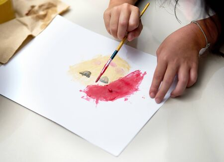 Kid hand make art activity with brush and coloring on paper on floor