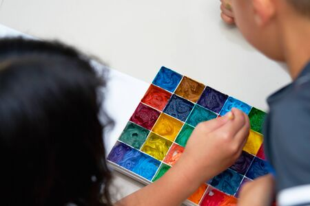 kids hold brush and plain paper with square color palette  for art work,tilt view