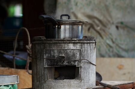 Old vintage firewood stove outside with pot for cooking food
