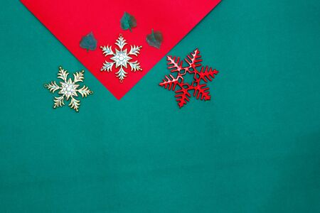 Christmas snow flake and leaves on Red green background,top  view and copy space