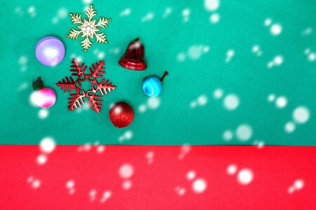 Christmas bauble, snowflake fruits and ring bell on Red green background with snow fall,top view with copy space Stock fotó
