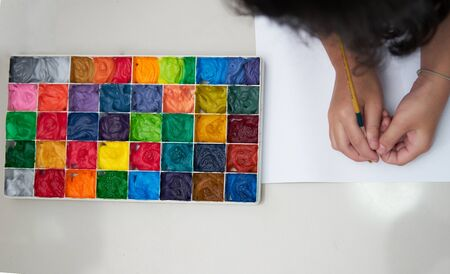 kid hold brush and plain paper with square color palette  for art work