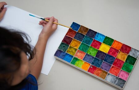 kid hold brush and plain paper with square color palette  for art work,top view Stock fotó