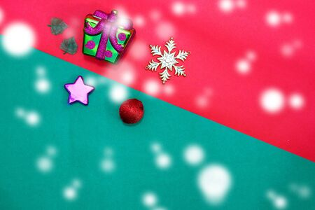 Christmas present,star,baubles,snow flake and leaves on Red green background with snow fall,top  view with copy space