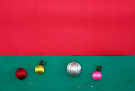 Baubles and fruits with golden string on green and red background for christmas with copy space Stock fotó