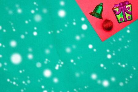 Present  box ,green bell and red bauble on red and green background with copy space for new year and christmas time with snow fall Stock fotó