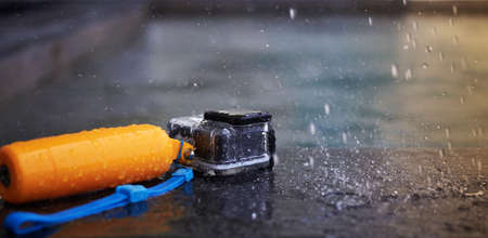 Action camera in waterproof case and floater grip on poolside with water rain drops in stop action and motion blur