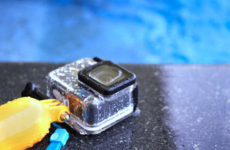 Action camera in waterproof case and floater grip on poolside and blur swimming pool