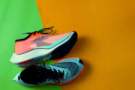 Blue and orange running shoes on green floor with copy test space,top view