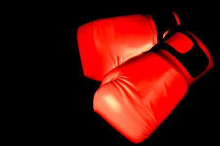Boxing glove in Red in punching  in black background with copy space Reklamní fotografie