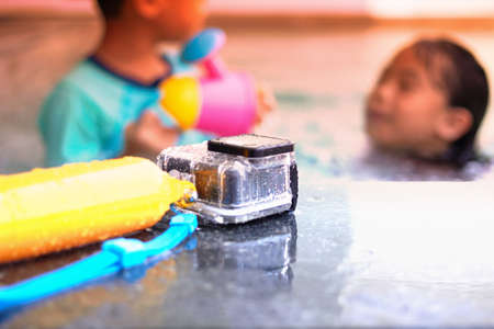 Action camera in waterproof case and floater grip on poolside and blur swimming pool and blur kids play in pool background with sun light Reklamní fotografie