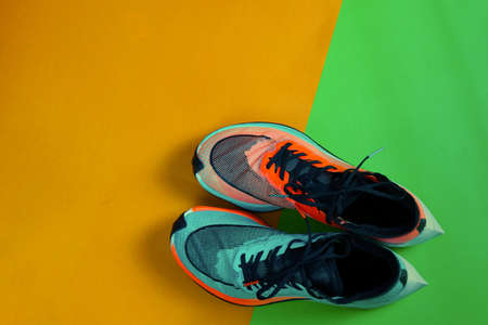 Blue and orange running shoe on green floor with copy test space,top Reklamní fotografie