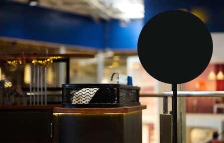 Black round shape mockup with stand beside counter bar shop Reklamní fotografie